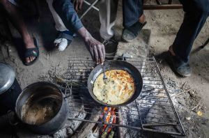 Sudanese residents cook pork on an open fire Image: Thom Davies