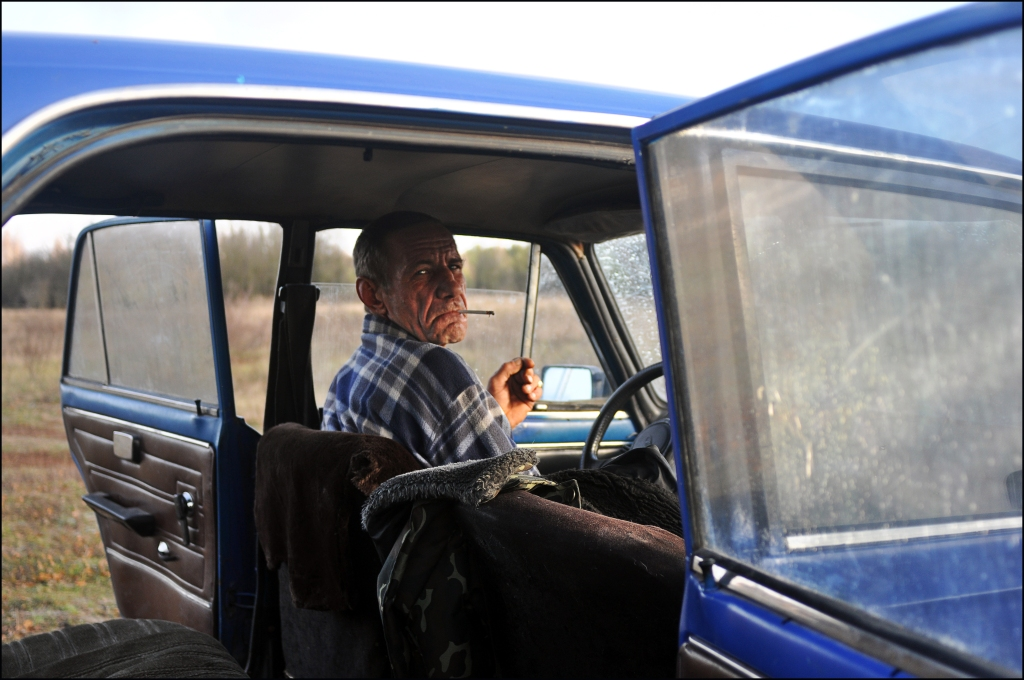 A former liquidator in his car near Chernobyl. (Credit: Thom Davies)