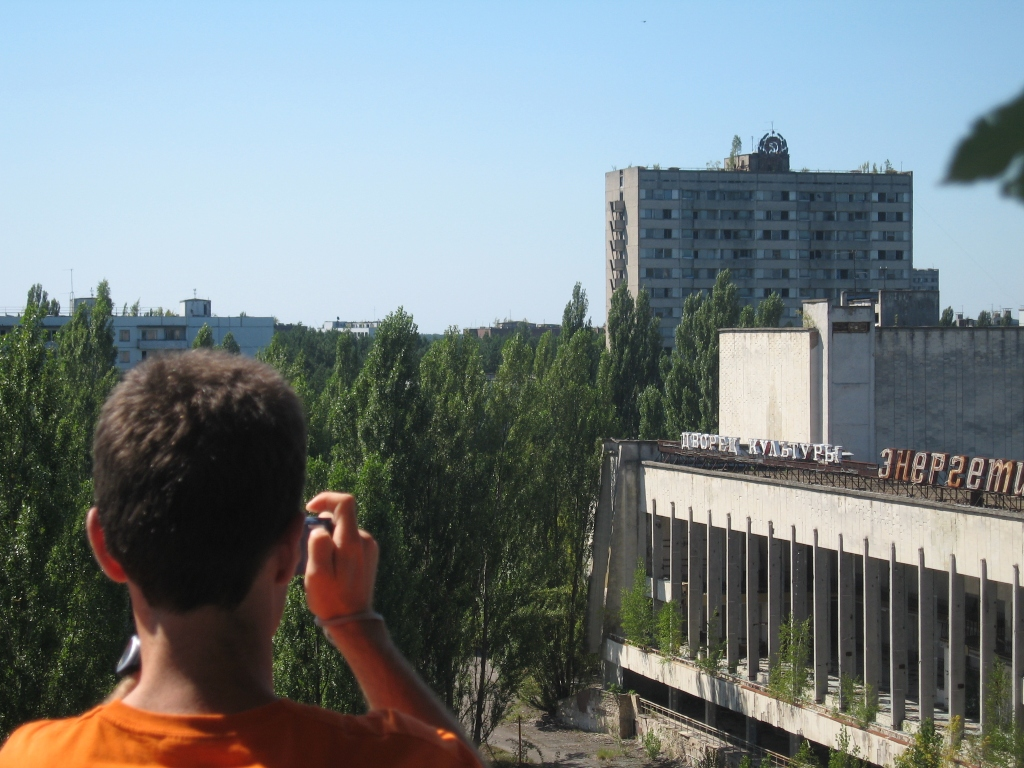 A tourist overlooking the overgrown city of Pripyat inside the Exclusion Zone