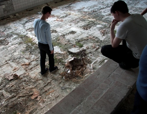 Tourists examine discarded film reel dumped in an abandoned swimming pool in the city of Pripyat